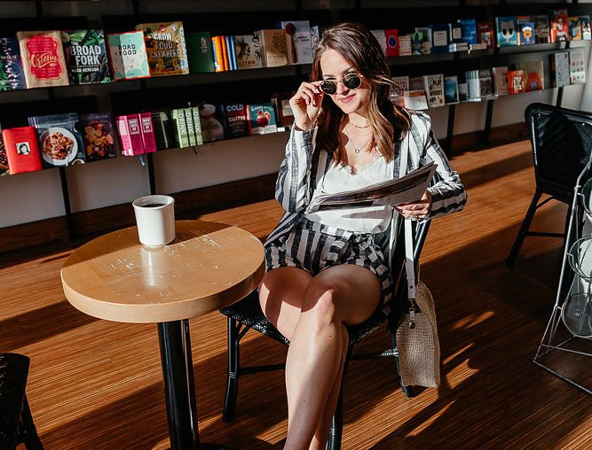Lauren Roscopf in a striped two piece set drinking coffee in a bookstore