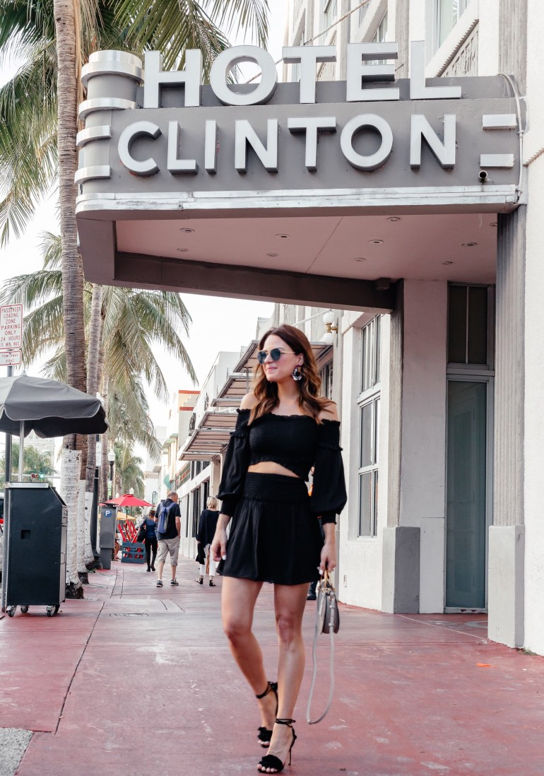 A Lo Profile wearing a black two piece Ali and Jay set from Shopbop with black Tony Bianco lace up ruffle heels, colorful earrings, a gray chloe round pixie bag, and blue Fendi sunnies from Solstice Sunglasses.