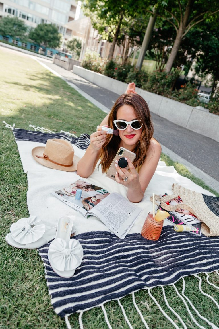 A Lo Profile having a day in the park reading magazines and using Supergoop mineral setting powder wearing a yellow topshop scallop cami, white hudson jeans shorts, bruno magali sandals, white sunglasses from nordstrom, a banana republic straw hat, and an ann taylor beach bag.