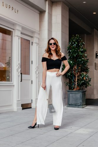 A Lo Profile wearing a black off-the-shoulder ruched crop top and white high waisted pants with slits and bold accessories from River Island