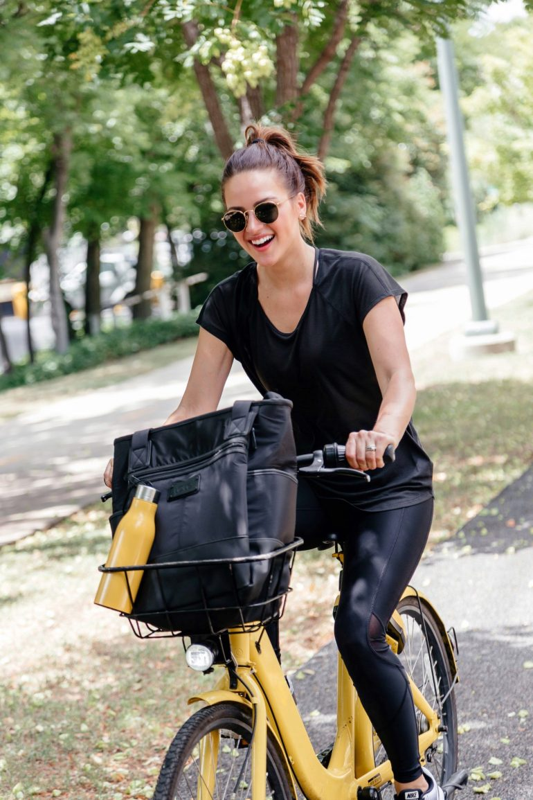 Lauren Roscopf from A Lo Profile wearing a black Lole workout look with a Lole bag and water bottle while riding her bike on the Katy Trail in Dallas.