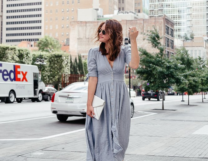 A Lo Profile sharing a roundup of Fourth of July Sales wearing a blue midi dress with white accessories.
