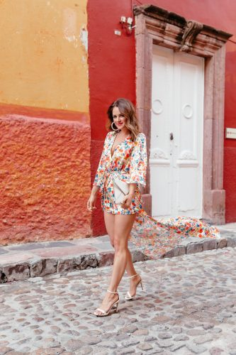 A Lo Profile wearing a maxi romper dress with a floral print from Tularosa via Revolve with white Steve Madden heels, white hoop earrings from Bauble Bar, and a white rebecca minkoff envelope clutch in San Miguel de Allende.