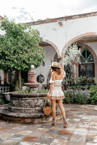 Dallas blogger A Lo Profile wearing a ruffled and embroidered mini dress by Lovers and Friends in San Miguel de Allende with a round Cult Gaia bag, a Sole Society hat, Sam Edelman tassel heels, blue Fendi sunglasses and gold Bauble Bar hoop earrings in San Miguel de Allende.