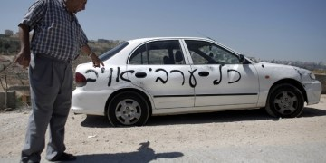 "A Palestinian man points at one of ten cars that were sprayed with racist slogans that read in Hebrew ""All the Arabs are enemies"" in the east Jerusalem neighborhood of Beit Hanina on June 23, 2014. AFP PHOTO / AHMAD GHARABLI"