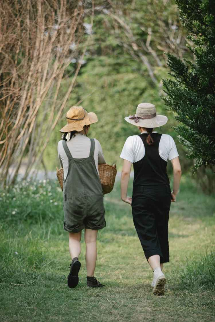 faceless gardeners strolling on path near grass in nature
