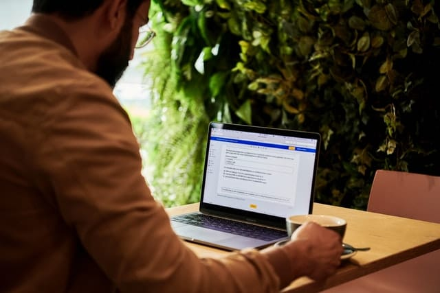 Seminar Transcription Service; A man holding a cup of tea while looking at his laptop