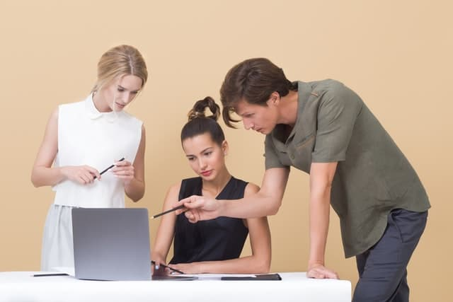 Seminar Transcription Service; a young man making suggestions while pointing at a laptop to two of his female colleagues