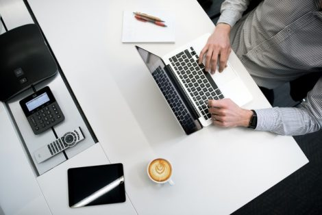 finance transcription tips; a minimalist desk with a person working on their laptop