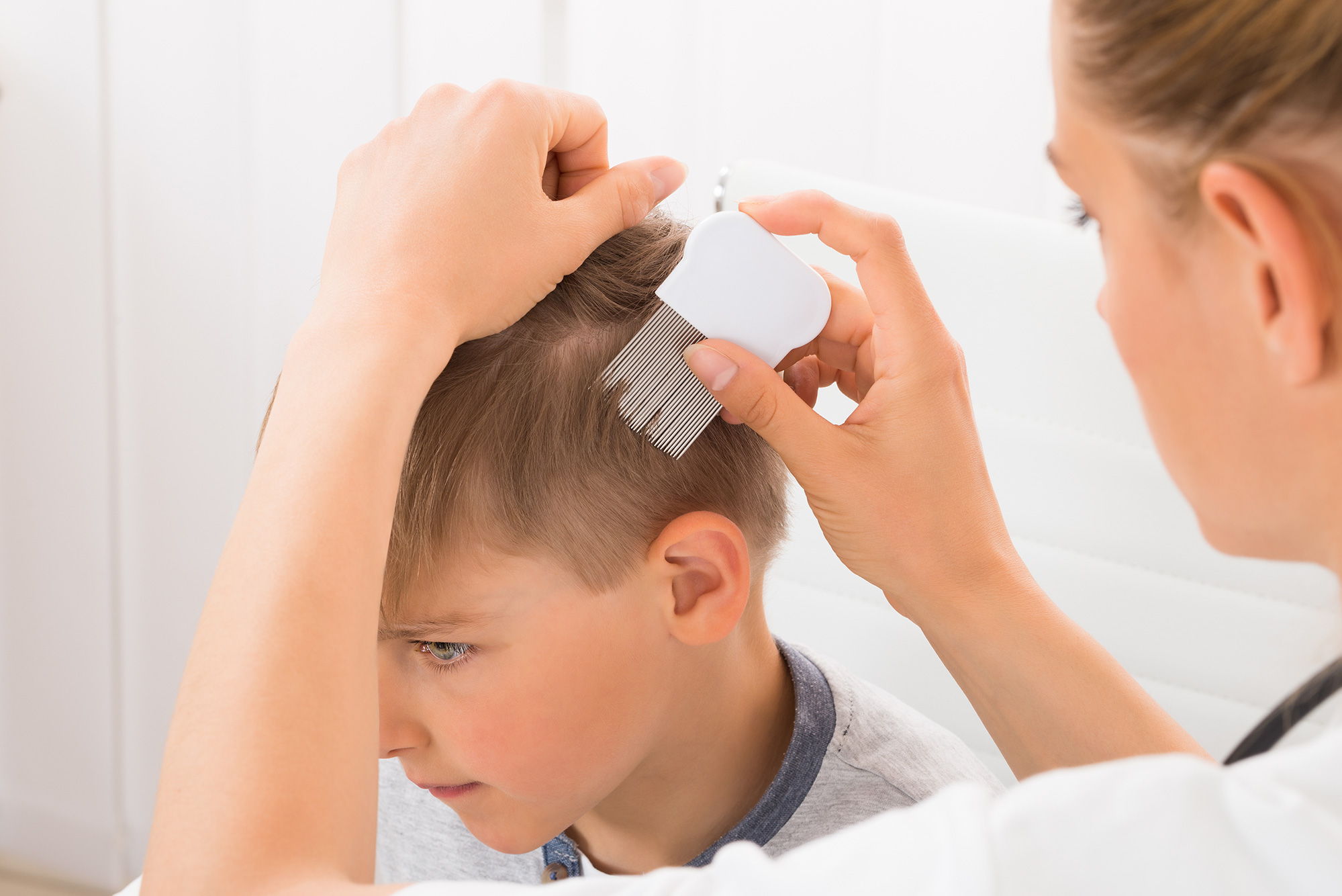 Mom looking for lice on her child's head using an anti-lice comb