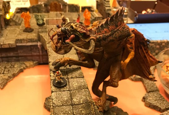 A dragon holds a miniature in its jaws as it climbs a stone bridge crossing a river of magma, all created with Dwarven Forge terrain.
