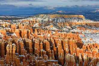 This is a view of the red rock formations in the Silent City area of the Bryce Amphitheater in Bryce Canyon National Park, Garfield County, Utah, USA. This spectacular view with a fresh dusting of snow looks northeast from Inspiration Point and shows Boat Mesa prominent in the center of the frame.