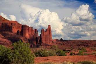 In this view the clouds cast fast-moving shadows on Fisher Towers, a red rock formation in the Professor Valley area northeast of Moab, Utah. This series of sandstone towers are a popular photographic subject as well for its rock climbing routes. This view looks northeast from Highway128, the Upper Colorado River Scenic Byway.