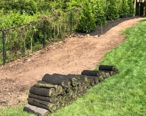 rolls of sod about to be laid on a slope