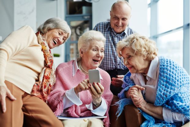 Personas mayores usando un móvil fácil felices