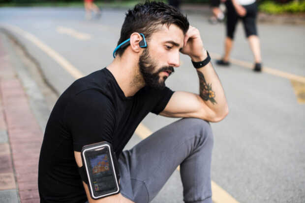 Hombre con audífonos Bluetooth y smartphone