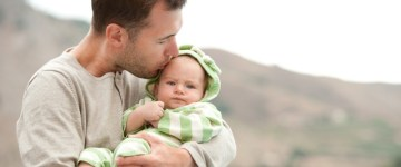 Счастливый отец держит на руках своего маленького сына и целует его