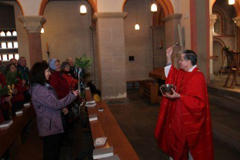 Pastor Gerd Belker segnet die Palmzweige der Pilger. Foto: Hubert Röser