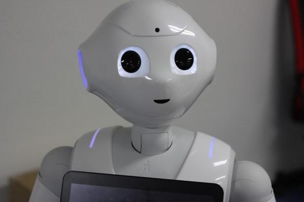 """Bild des Roboters Pepper. Er ist weiß, hat ein """"Gesicht"""" mit großen dunklen Augen."""