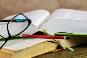 Auf einem Tisch liegen zwei aufgeschlagene Bücher, eine Brille und Bleistifte