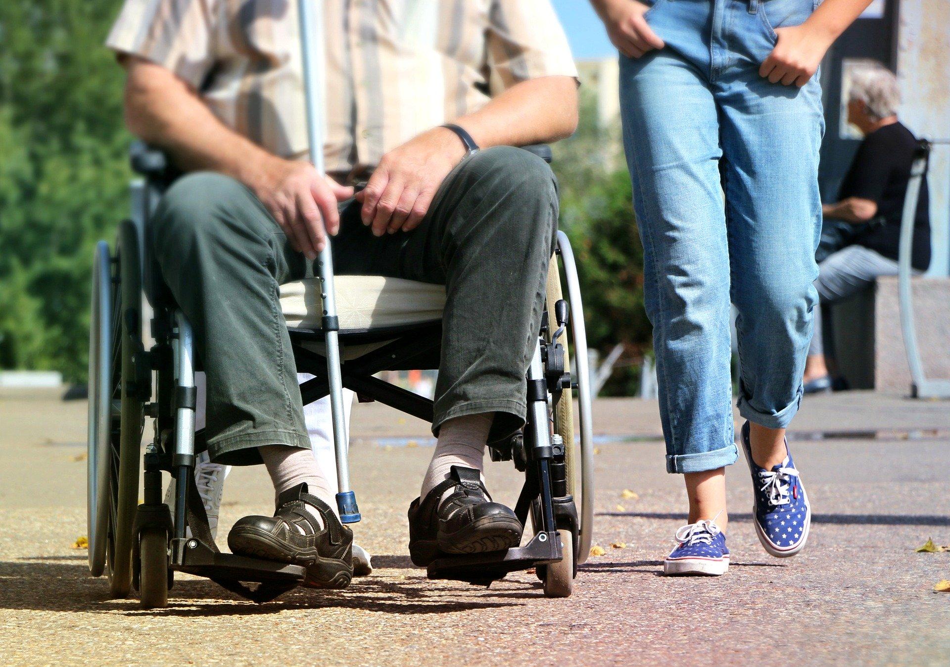 Links Mann im Rollstuhl, rechts geht eine jüngere Person, man sieht nur die Beine in Jeans