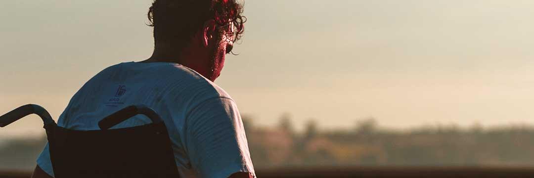 Titelbild des Beitrags. Zu sehen ist ein Mann, der auf seinem Rollstuhl dem Sonnenuntergang entgegen fährt.