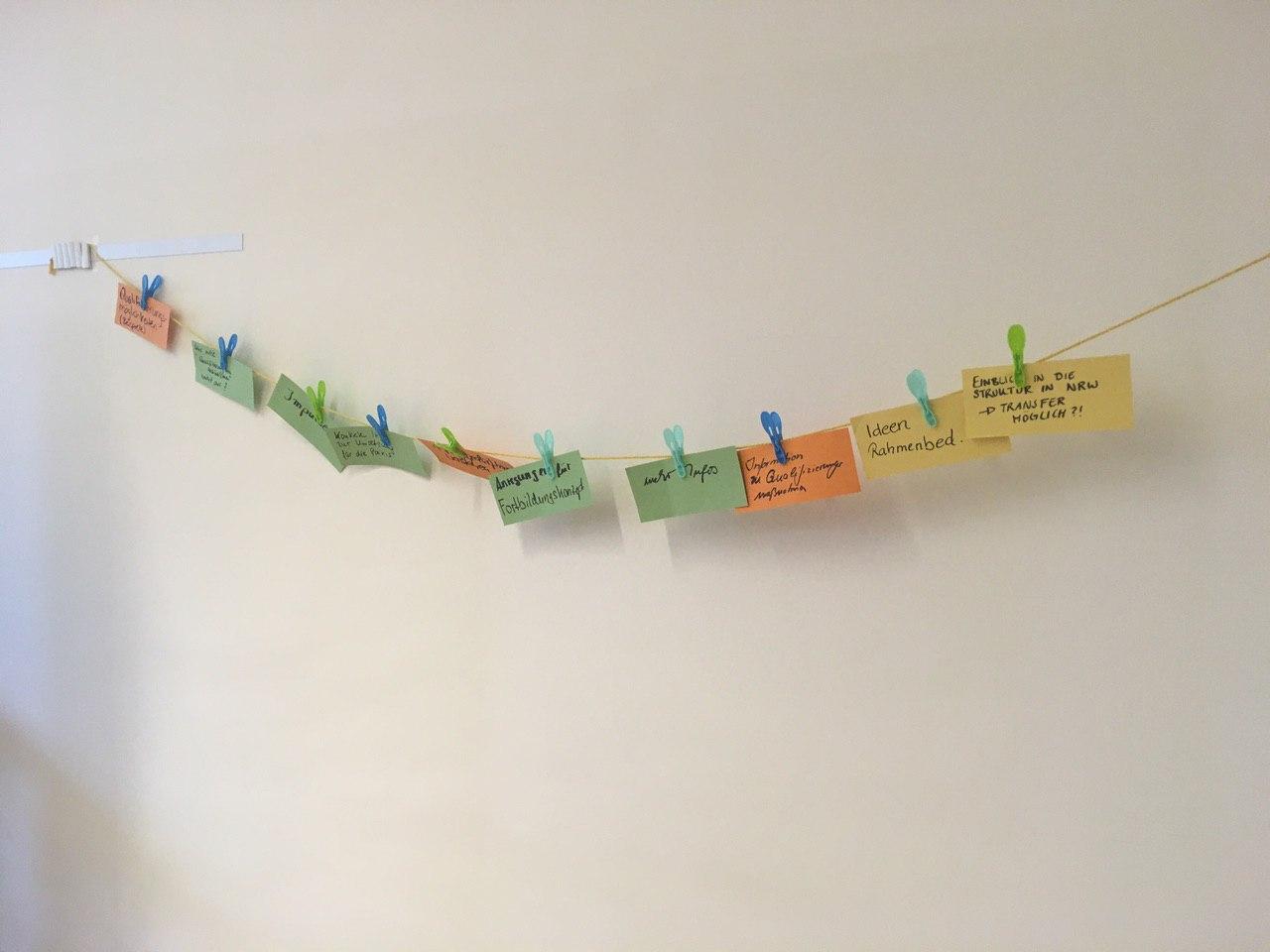 Wäscheleine mit Moderationskarten, auf denen die teilnehmenden ihre Erwartungen an den Workshop notiert haben