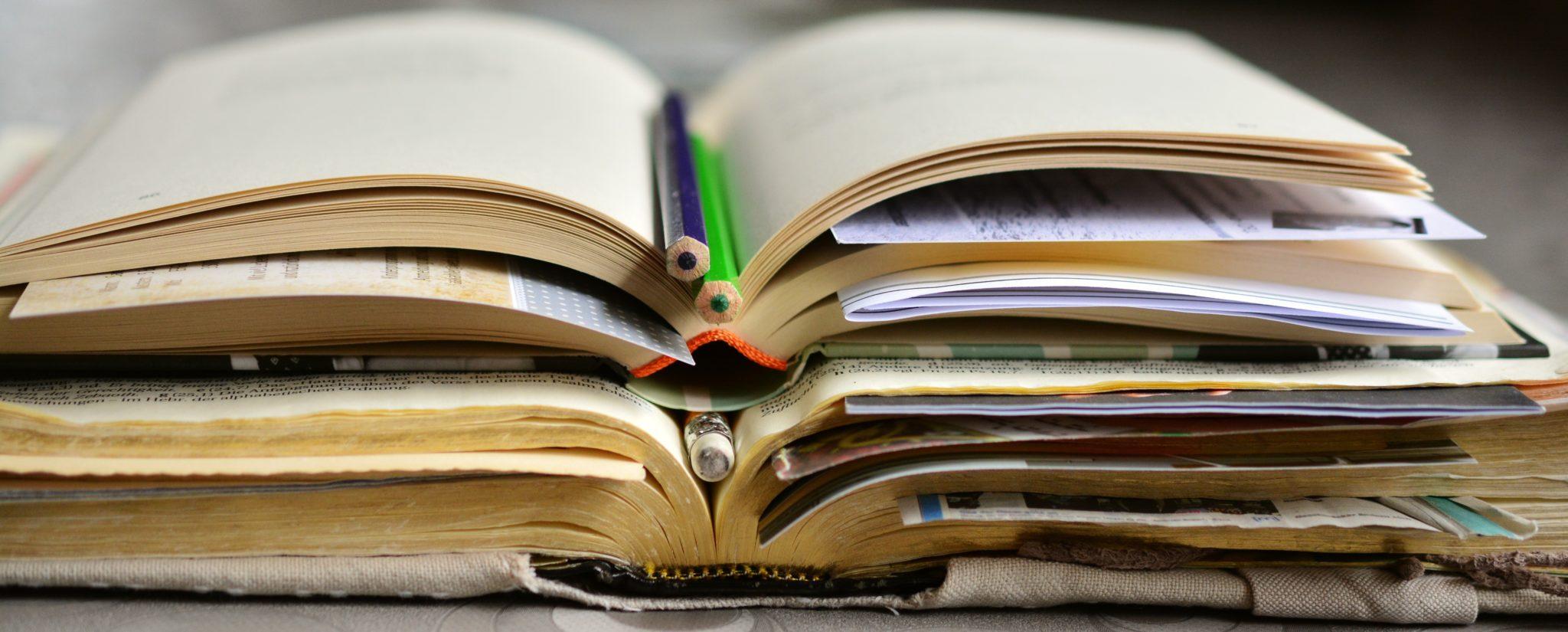 Gestapelte Bücher mit Stiften und Notizen darin