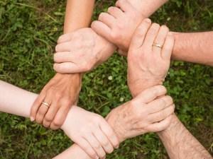 Sech Hände berühren sich im Kreis.