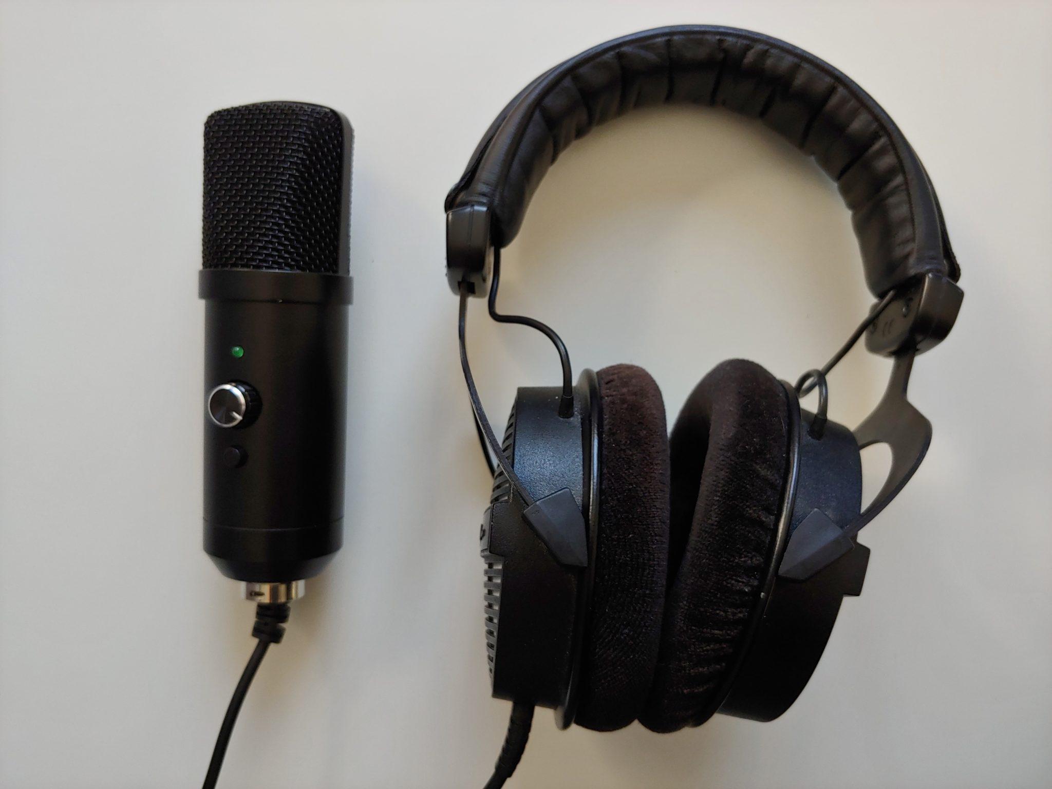 Ein Mikrofon und ein Kopfhörer liegen nebeneinander auf dem Tisch