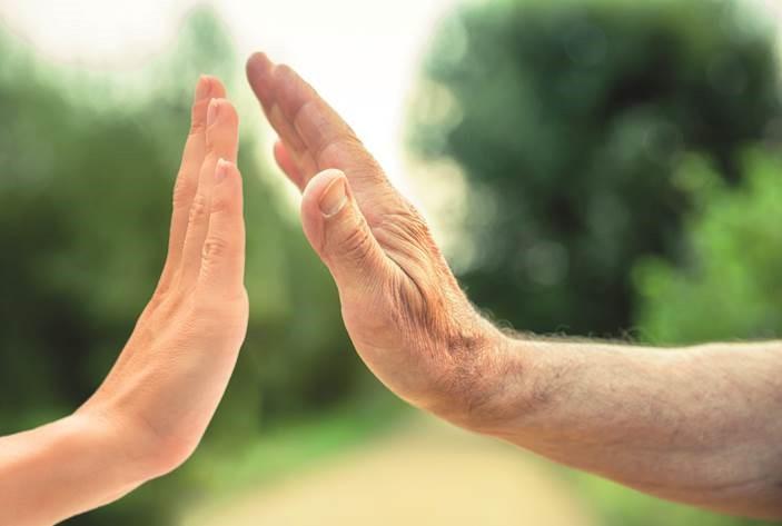 Alte und junge Hand schlagen einander ab. Ähnlich dem gib mir fünf.