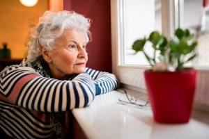 Eine ältere Frau schaut traurig aus dem Fenster.