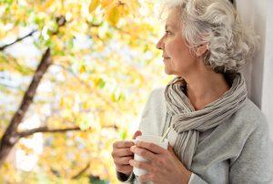 Eine Seniorin schaut alleine mit einer Tasse Kaffe aus dem Fenster. Sie macht den Eindruck, dass sie einsam ist.