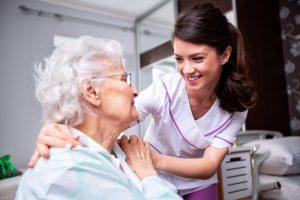 Die Mitarbeiterin eines ambulanten Pflegedienstes lächelt eine Seniorin an, während die ihren Arm um sie legt.