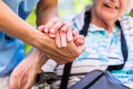 Ein junger Pfleger hält die Hand einer Seniorin. Die Seniorin lacht.