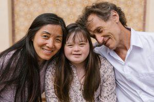 Gruppenbild von Mutter, Tochter mit Trisomie 21 und Vater
