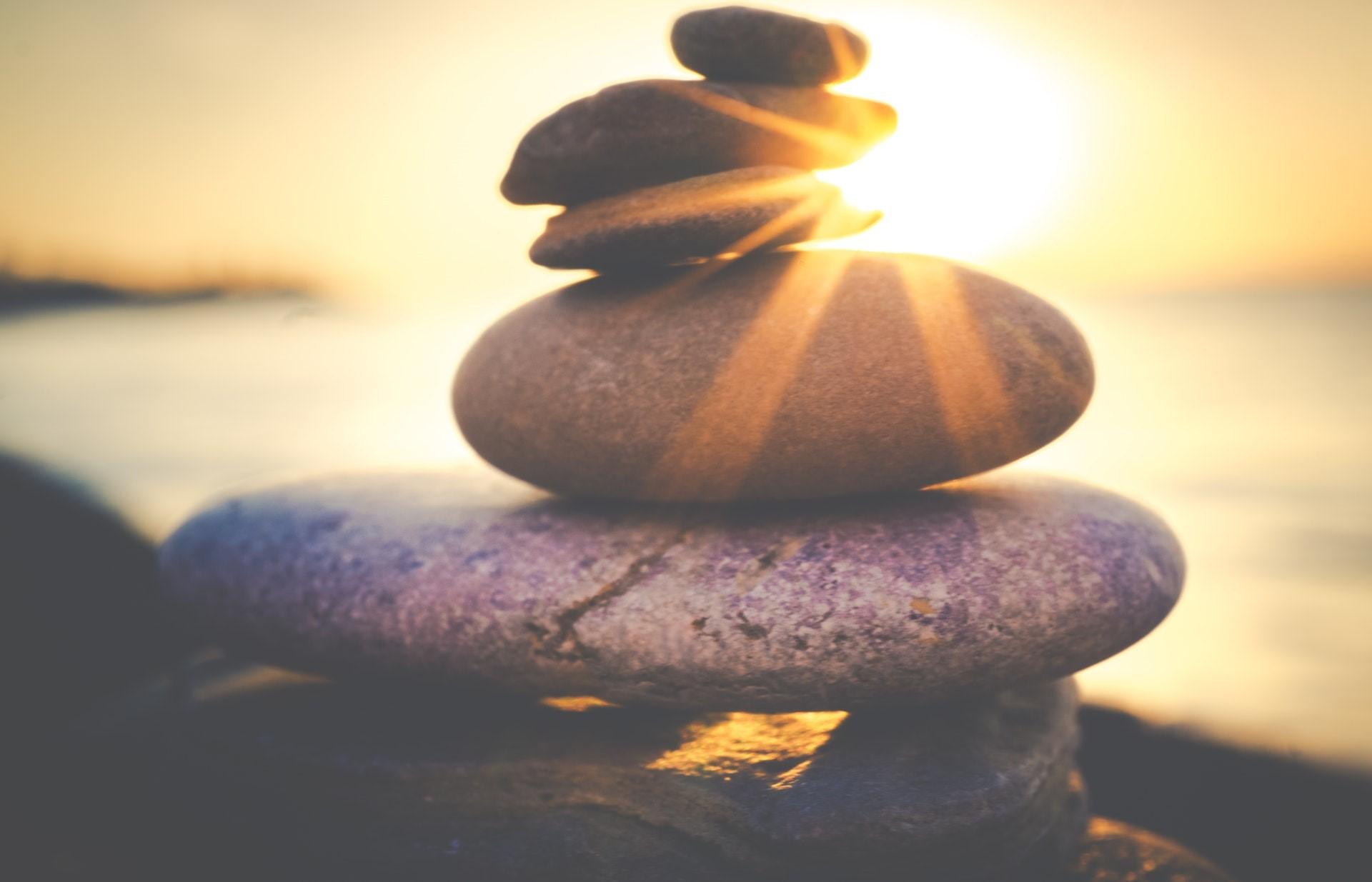 Kleine, runde Steine sind überinander gestapelt und ausbalanciert. Im Hintergrund geht die Sonne unter.