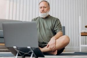 Ein Mann sitzt im Schneidersitz auf einer Yoga-Matte. Vor ihm ist ein Laptop aufgebaut.