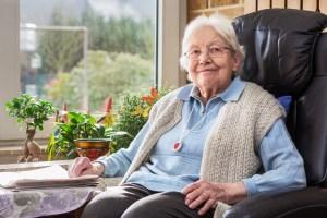 Eine Seniorin sitzt zuhause in ihrem Sessel.