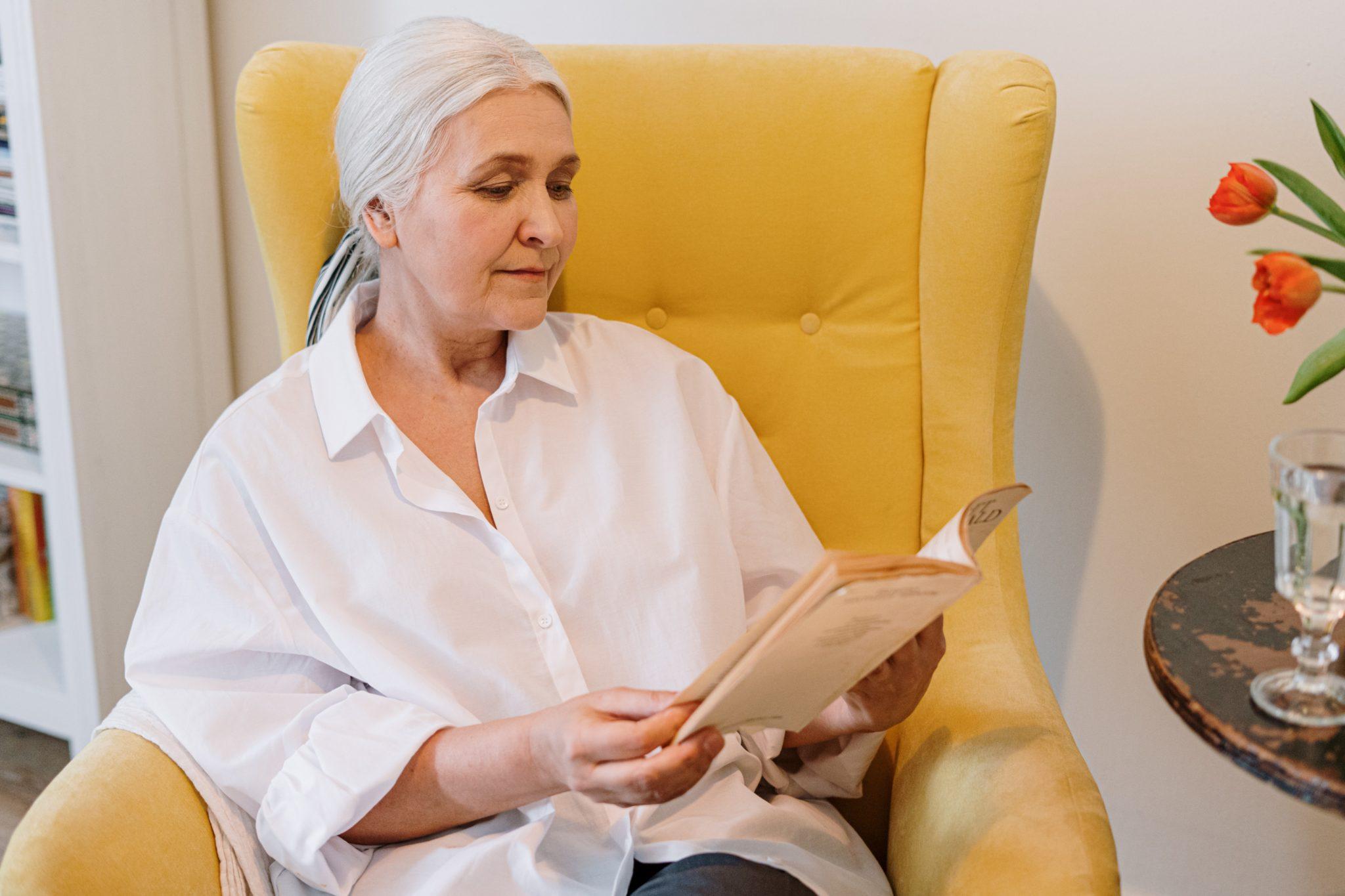 Ältere Dame sitzt in gelbem Sessel und liest ein Buch