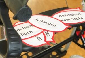 """Symbolbild eines Rollators, darauf liegen ausgedruckte Sprechblasen mit texten wie """"Ankleiden"""", """"Vom Boden hoch"""", """"Aufstehen vom Stuhl"""""""