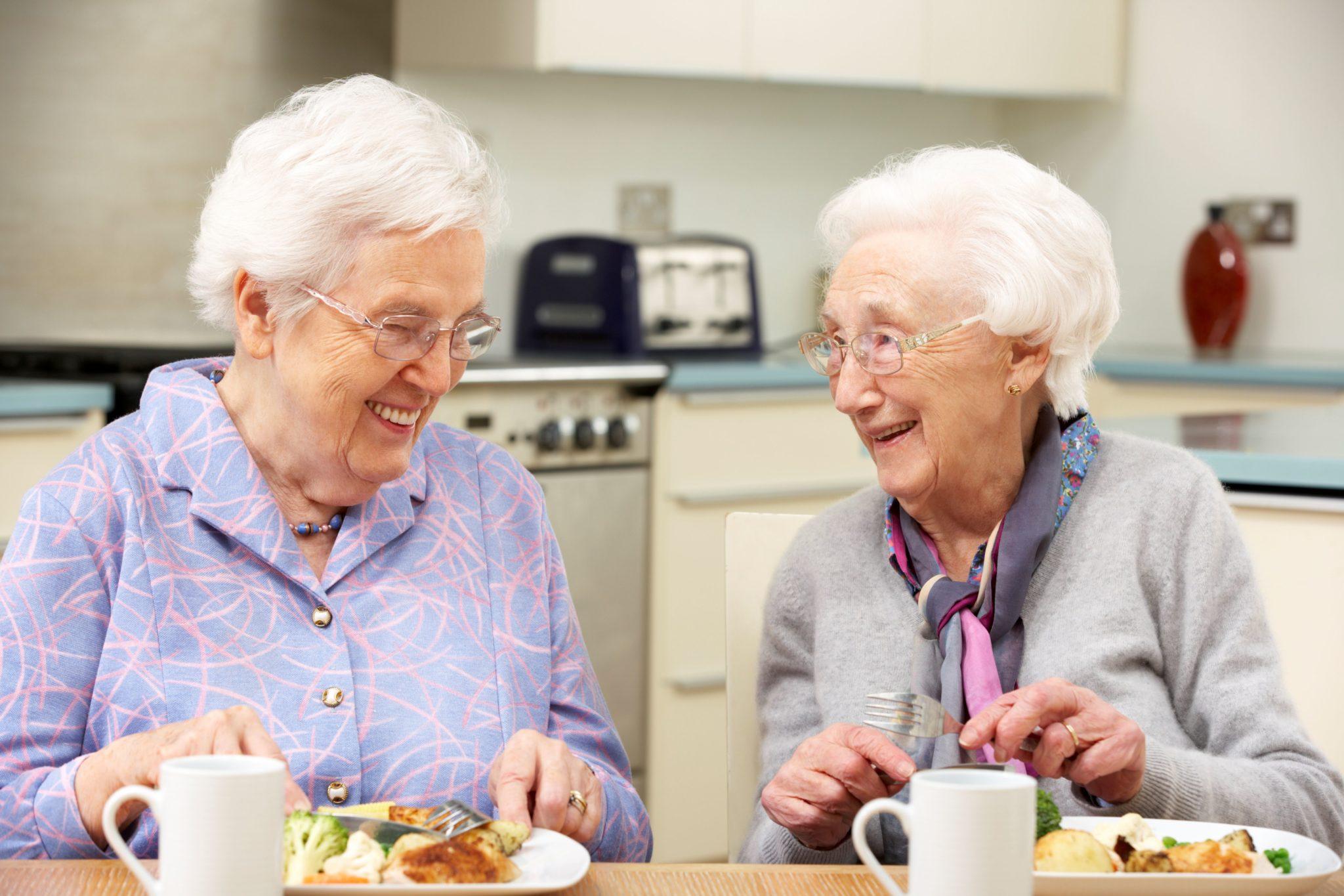Zwei Seniorinnen essen gemeinsam zu Mittag.