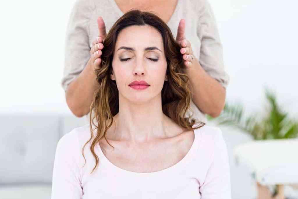 Dame som sitter med lukkeden øyne og annen person holder sine hender på hver side av hennes hode