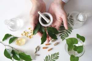 Forskjelige urter og en morter i holdt av to hender