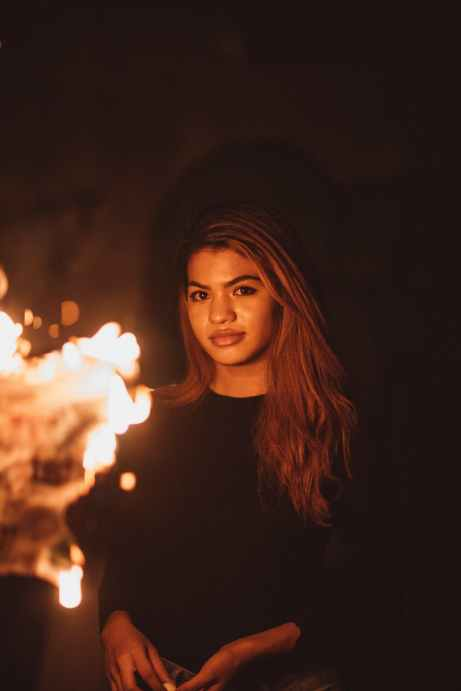 woman smiling in front of fire