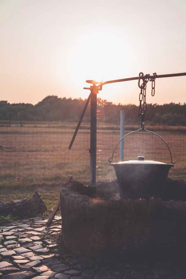 gray steel cooking pot hanged by brown steel chain