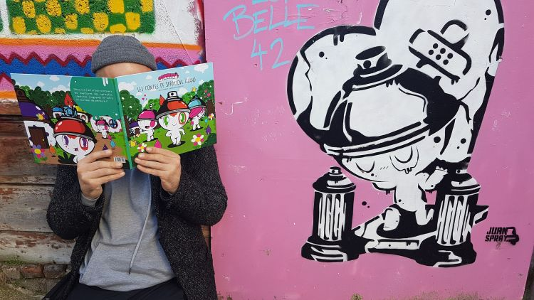 l'artiste Juan Spray en train de lire les contes de SprayLove Island dans la rue devant un de ses pochoirs