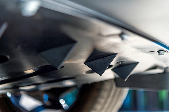 Disse små trekanter kommer fra flyindustrien og sænker støjen i kabinen ved at styre luftstrømmen under bilen