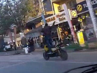 Motosikletin üzerinde telefonla konuşup ayağa kalktı