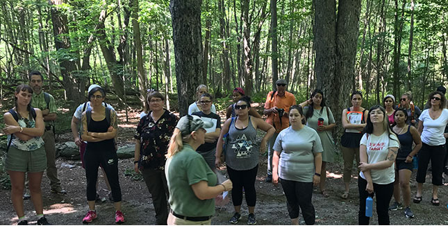 Students stand around a presenter in a forest